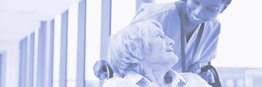 A nurse pushes a woman along in a wheelchair