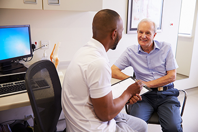 A physiotherapist chats with his patient
