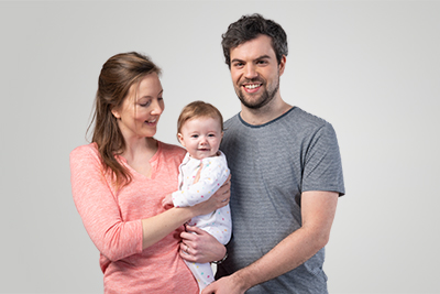 A smiling couple with a baby